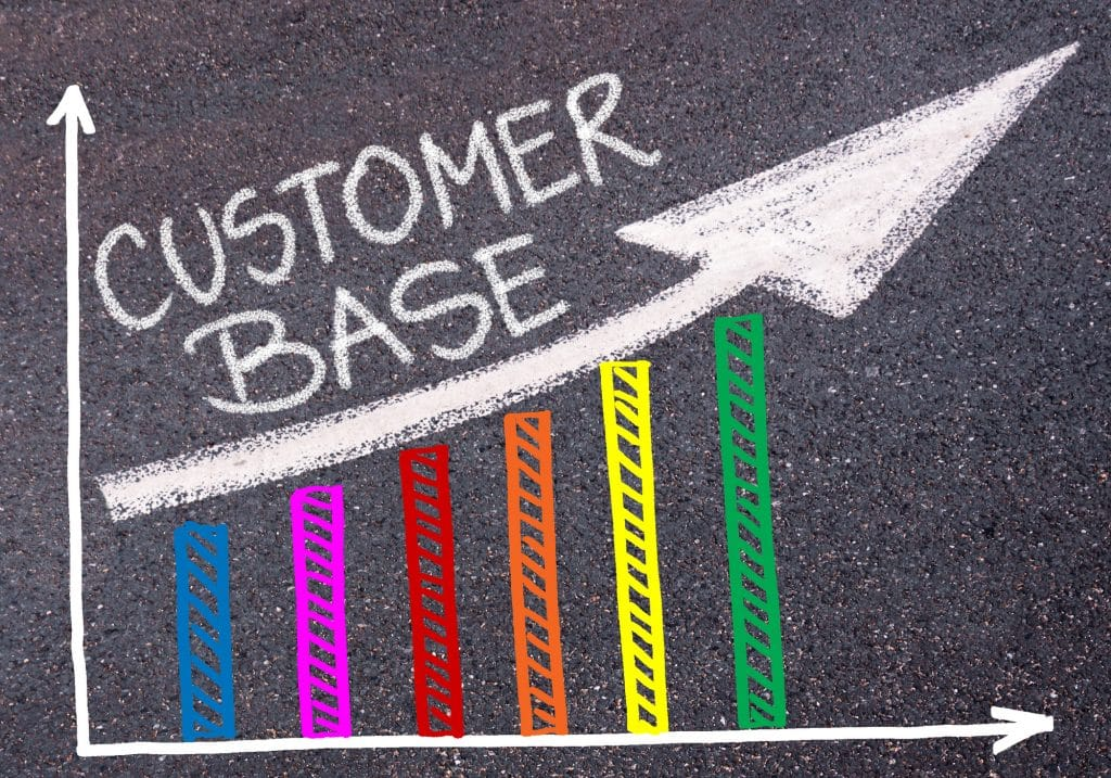 CUSTOMER BASE written with chalk on tarmac over colourful graph and rising arrow