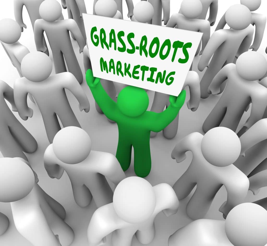 "A green figure holding a sign up that says ""Grass Root Marketing"" in a crowd"