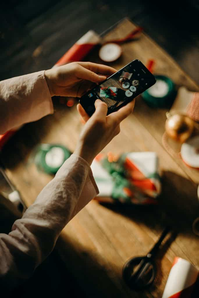 woman holding a mobile phone using it to take a photo of a christmas present
